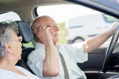 Homme supérieur conduisant la voiture et parlant au téléphone Photographie stock libre de droits