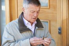 Homme supérieur confus essayant de trouver la clé de porte Photographie stock