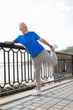 Homme supérieur convenable s'étirant sur le pont Photographie stock libre de droits