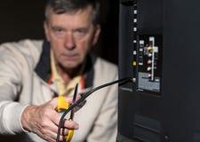 Homme supérieur coupant la corde sur son paquet TV par câble Photo libre de droits