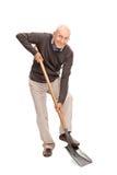 Homme supérieur creusant avec une pelle Photo stock