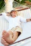 Homme supérieur détendant dans l'hamac de plage Photos stock