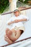 Homme supérieur détendant dans l'hamac de plage Photographie stock libre de droits
