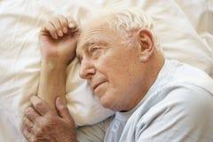 Homme supérieur détendant dans le lit Photographie stock