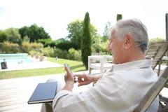 Homme supérieur détendant dehors avec un livre Photos libres de droits
