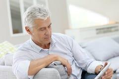 Homme supérieur détendant sur le sofa tenant le comprimé Photos libres de droits