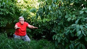 Homme supérieur dans des vêtements sport, peut-être un retraité, faisant des postures accroupies dans l'arrière-cour ou dans le j clips vidéos