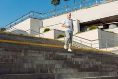 Homme supérieur dans l'équipement sportif fonctionnant en bas des escaliers Photo stock