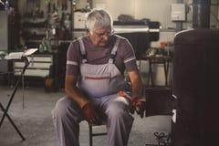 Homme supérieur dans l'atelier L'homme s'est trouvé le feu dans l'atelier Photographie stock libre de droits