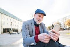Homme supérieur dans la ville avec le téléphone intelligent, textotant Image libre de droits