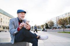Homme supérieur dans la ville avec le téléphone intelligent, textotant Photographie stock