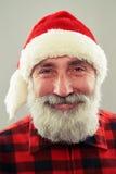 Homme supérieur dans le chapeau de Santa au-dessus du fond gris-clair Photographie stock