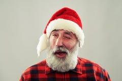 Homme supérieur dans le chapeau de Santa regardant l'appareil-photo et cligner de l'oeil Photographie stock libre de droits