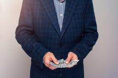 Homme supérieur dans le costume comptant l'argent dans des mains Photographie stock libre de droits