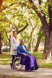 Homme supérieur dans le fauteuil roulant avec l'infirmière en parc Photographie stock