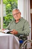 Homme supérieur dans le fauteuil roulant avec le livre Photos stock