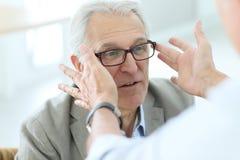 Homme supérieur dans le magasin optique essayant sur des lunettes image libre de droits