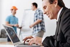 Homme supérieur dans un costume travaillant sur son ordinateur portable Photo libre de droits
