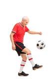 Homme supérieur dans un débardeur rouge jonglant un football Image stock