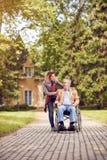 Homme supérieur dans un fauteuil roulant appréciant l'air frais dans un esprit de jour ensoleillé Images stock