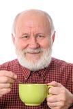 Homme supérieur de Cheerfull avec la tasse verte, d'isolement sur le blanc Photographie stock