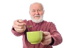 Homme supérieur de Cheerfull avec la tasse verte et la cuillère à café, d'isolement sur le blanc Photos stock