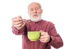 Homme supérieur de Cheerfull avec la tasse verte et la cuillère à café, d'isolement sur le blanc Image stock
