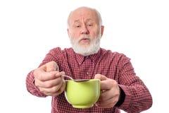 Homme supérieur de Cheerfull avec la tasse verte et la cuillère à café, d'isolement sur le blanc Image libre de droits