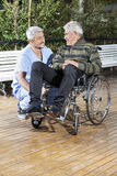 Homme supérieur de Looking At Disabled de physiothérapeute dans le fauteuil roulant Photographie stock libre de droits