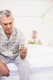 Homme supérieur de souffrance prenant des pilules Photographie stock libre de droits