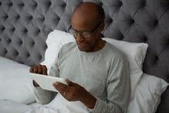 Homme supérieur de sourire à l'aide du comprimé numérique tout en se reposant sur le lit Image libre de droits