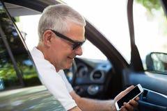 Homme supérieur de sourire à l'aide du téléphone intelligent dans la voiture Photos libres de droits