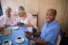 Homme supérieur de sourire à l'aide du téléphone portable tout en ayant le thé avec des amis Image libre de droits