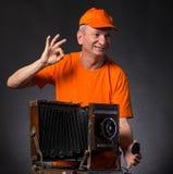 Homme supérieur de sourire avec l'appareil-photo en bois de photo de vintage Photographie stock