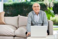 Homme supérieur de sourire avec l'ordinateur portable à la maison de repos Photographie stock libre de droits