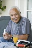 Homme supérieur de sourire avec le jus d'orange Photographie stock libre de droits