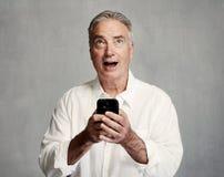 Homme supérieur de sourire avec le smartphone photo libre de droits