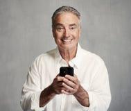 Homme supérieur de sourire avec le smartphone photo stock