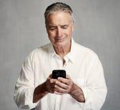 Homme supérieur de sourire avec le smartphone photographie stock
