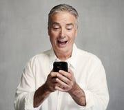 Homme supérieur de sourire avec le smartphone photos libres de droits