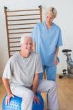 Homme supérieur de sourire avec son thérapeute Photographie stock libre de droits