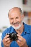 Homme supérieur de sourire avec un appareil-photo Images libres de droits