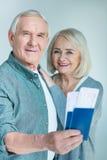 Homme supérieur de sourire montrant des passeports et des billets avec l'épouse tout près, concept de déplacement Photos stock