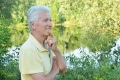 Homme supérieur de sourire posant en parc d'été photo stock