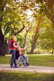 Homme supérieur de temps de famille dans le fauteuil roulant et la fille en parc Photos stock