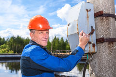 Homme supérieur de travailleur tournant le commutateur électrique Photo stock