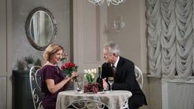 Homme supérieur donnant le bouquet des fleurs à son épouse banque de vidéos