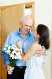 Homme supérieur donnant le groupe de fleurs à la femme Photo stock