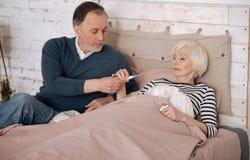 Homme supérieur donnant le thermomètre à son épouse malade Images stock