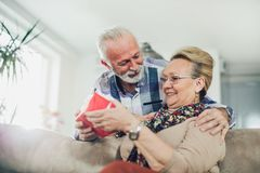 Homme supérieur donnant un présent à sa femme Image stock
